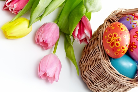 Image of colored Easter eggs in basket and bunch of tulips near by photo