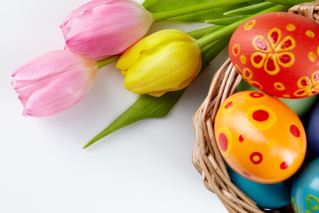 creative egg painting: Image of colored Easter eggs in basket and bunch of tulips near by