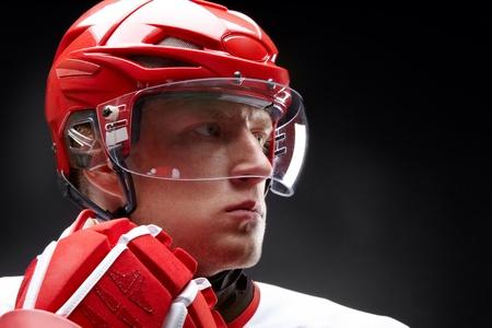 Retrato de un jugador de hockey contra el negro backround Foto de archivo