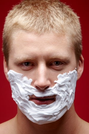 Young man with foam on his face being ready to shave photo