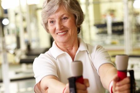 Tilt up of a pretty mature lady working out at gym Stock Photo - 12326496