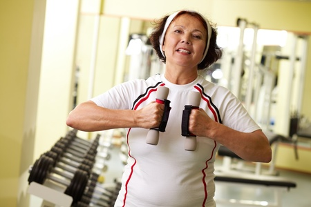 keeping fit: Persistent elder woman with dumbbells keeping fit