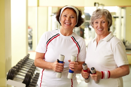 elderly exercise: Two cheerful ladies looking at camera holding dumbbells