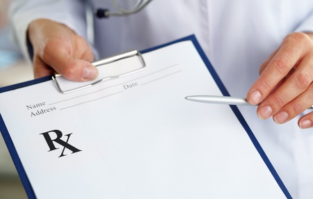 Hand of female doctor with pen pointing at clipboard photo
