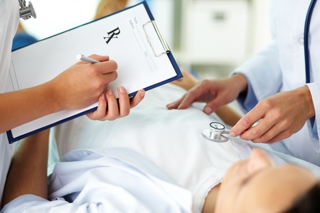 medical personal: Close-up of female doctors during medical treatment of patient in hospital Stock Photo