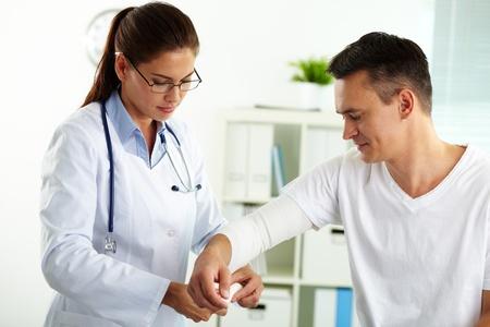 Doctor patient: Retrato de mujer m�dico conf�a en dar los primeros auxilios a paciente de sexo masculino en el hospital Foto de archivo