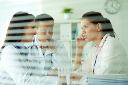 Portrait of confident practitioners consulting patient in medical office photo