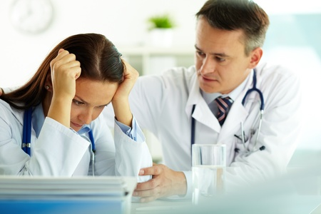 doctor stress: Portrait of tired woman touching temples with male colleague reassuring her