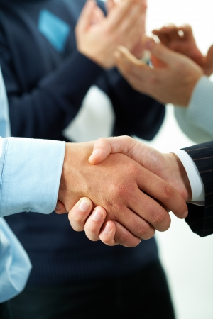 handshaking: Close-up of males handshaking with applauding people on background Stock Photo