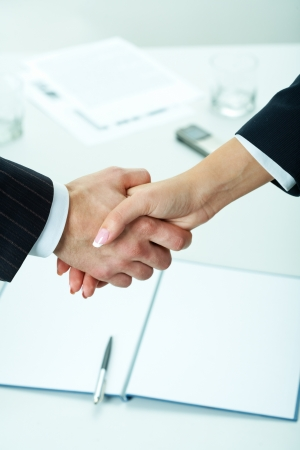 Close-up of two shaking hands with business documents on background photo