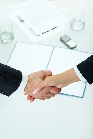 handshaking: Close-up of two shaking hands over workplace with business documents on it
