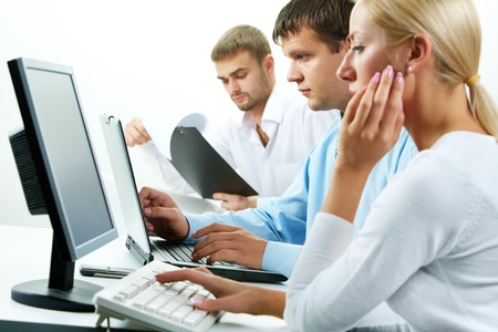 Image of serious business partners typing in working environment   photo