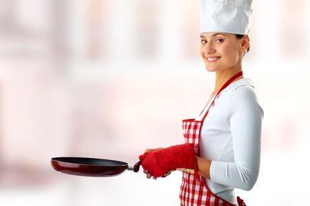 Portrait of happy female with frying pan looking at camera on creative background  photo