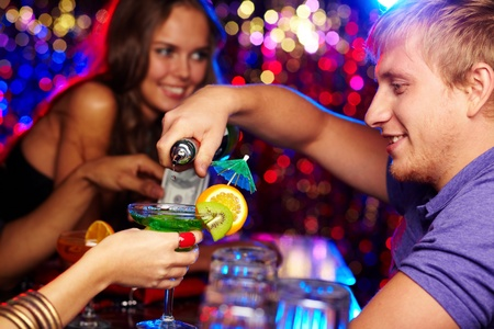bartender: Cheerful bartender pouring cocktails at a party