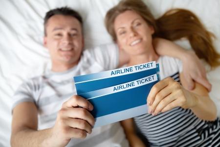 middle class: Feliz pareja joven tumbado en la cama con los billetes de avión en las manos Foto de archivo