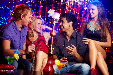 joven fumando: Los amigos felices bebiendo c�cteles y Kalian fumar en la discoteca Foto de archivo