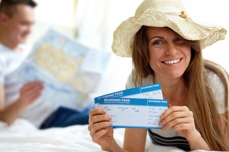 Happy woman in hat showing flight tickets photo