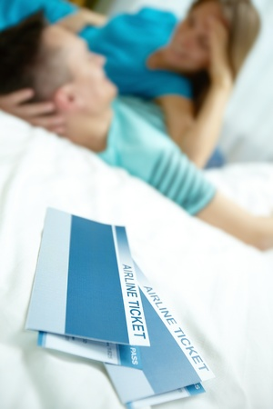 Image of airline tickets with happy young couple lying on bed Stock Photo - 12327648