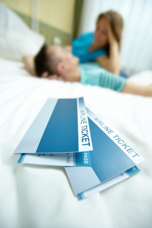 boarding card: Image of airline tickets on bed with happy young couple at background