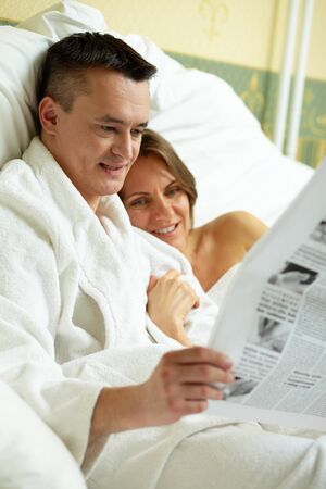 Married couple lying in bed and reading newspaper photo