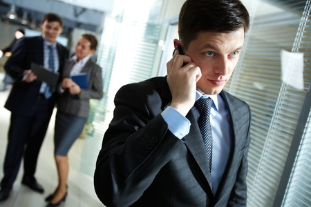 Businessman speaking on the phone, his colleagues discussing business matters in the background photo