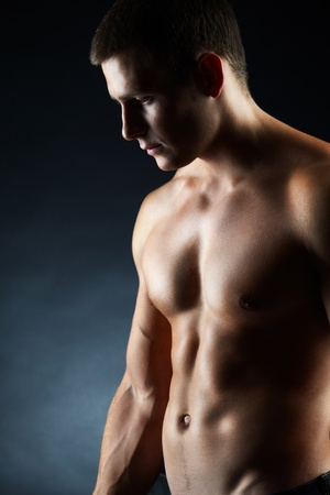 nude man: A portrait of a handsome young man without a shirt against dark background