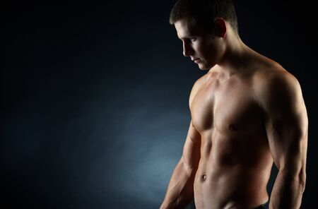 A portrait of a hot guy man without a shirt against dark background with copyspace Stock Photo - 12327708