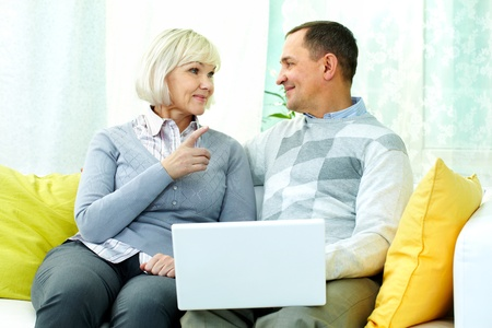 Portrait of mature man and his wife chatting at home during computer work Stock Photo - 12328669