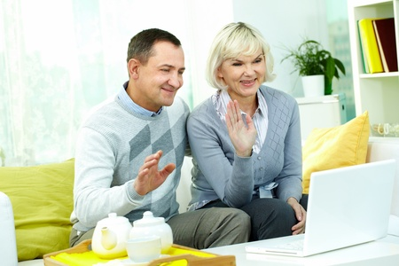 Portrait of mature man and his wife chatting with their friends through internet photo