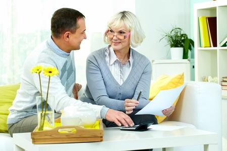 Retrato de hombre maduro y su esposa haciendo la revisión financiera en el hogar