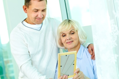 Portrait of mature man and his wife looking at photograph in frame Stock Photo - 12328558
