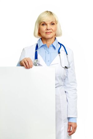 Positive female doctor holding a poster isolated on white background photo
