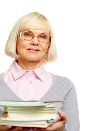 Beautiful mature lady holding a pile of notebooks books and smiling at camera photo