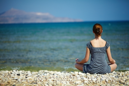 Young woman sitting on the beach enjoying peaceful moment photo