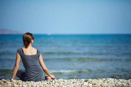 mujeres sentadas: Joven mujer sentada en la playa mirando el mar y el cielo
