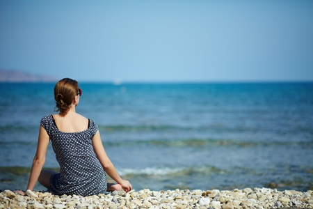 seated: Young woman sitting on the beach looking at the sea and sky