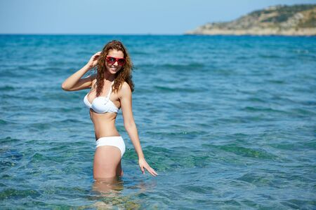 Young beauty standing in water and smiling photo