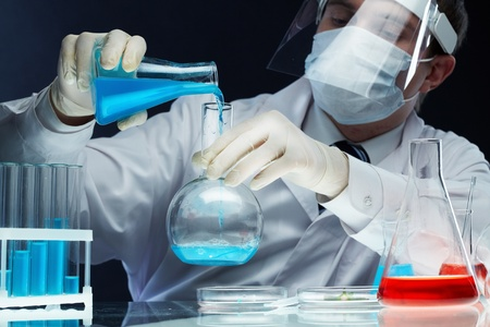 Scientist pouring fluid substances from one beaker into another photo