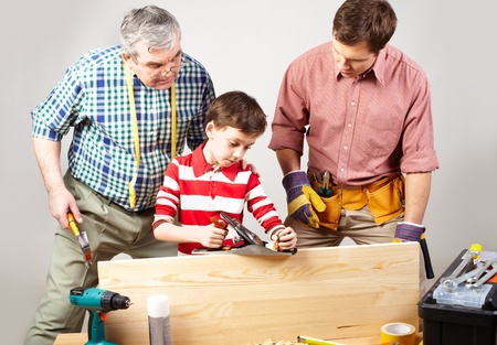 looked: Little boy trying his best in a woodshop being looked after by his dad and grandfather