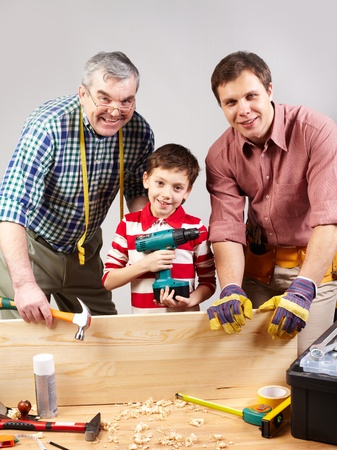 Vertical shot of three multigenerational guys working in a woodshop and smiling at camera photo