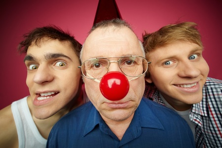 prank: Three men of different age looking at camera, fool�s day celebration Stock Photo