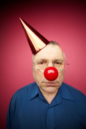 Portrait of unhappy man with a red nose and in a cone cap on fool�s day photo