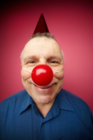 Portrait of a cheerful man with red nose smiling at camera on fool�s day photo