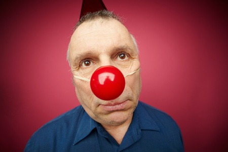 Portrait of unhappy man with a red nose celebrating all fools day photo