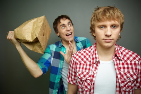 Crazy guy being ready to explode paper bag behind his friend back photo