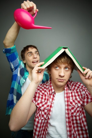 Freaky guy pouring water over his friend hiding under a book, fool�s day celebration photo