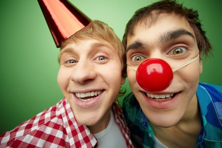 Two crazy guys making faces at camera on fool�s day, isolated on green background photo