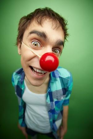 tonto: Primer plano de un chico un poco loco, con nariz de payaso celebra día de los inocentes Foto de archivo