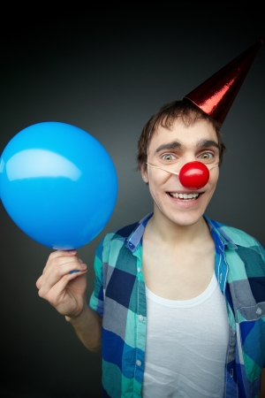 Happy guy holding a balloon and smiling crazily at camera celebrating fool�s day photo
