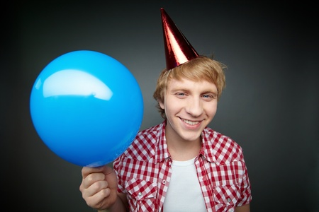 Blonde guy ready to let go of balloon smiling at camera celebrating fool�s day photo